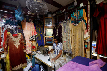 A tailor works on a sewing machine while stitching a ladies dress in a shop at market in Karachi