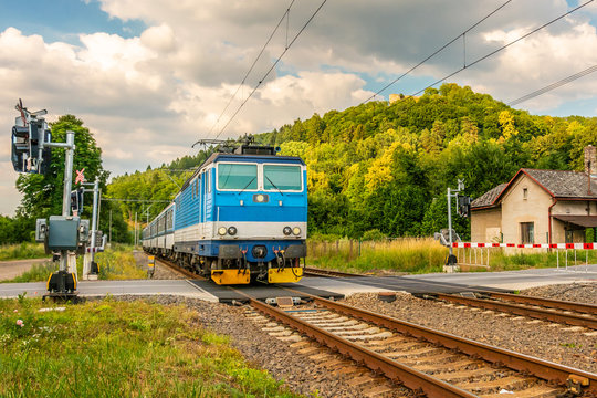 The blue electric train arriving at the crossing with the barriers. A train running through the green valley. Rail transport in the Czech Republic. A sunny day on the railroad