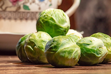 Brussel sprouts on a wooden table with a coffee cup