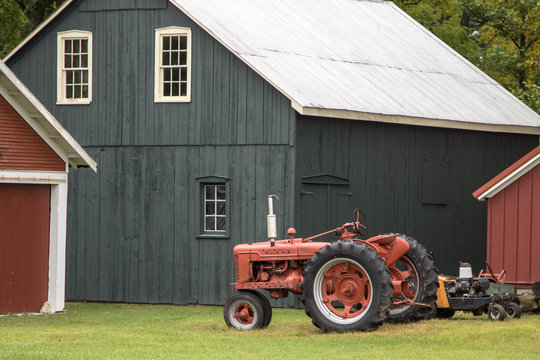 Farming Background. Red antique tractor and traditional barn in the American Midwest.