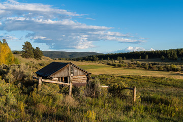 Old rustic log cabin overlooking a landscape of ranchland, fields, forest, and hills in northern New Mexico in late afternoon sunlight