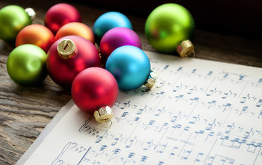 Altes handgeschriebenes Notenblatt mit vielen bunten Weihnachtskugeln, Weihnachten, xmas