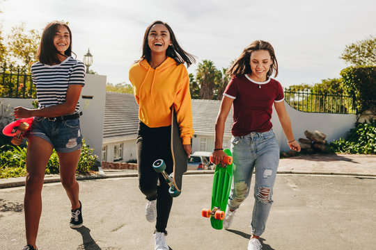 Teenage girls walking on street holding skateboards