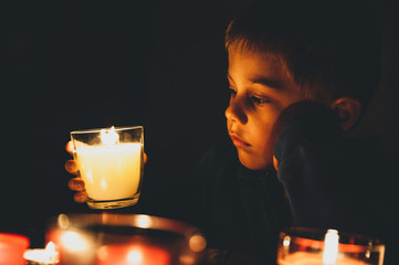 Child in the dark looks at candles