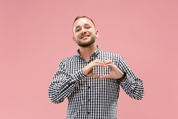 I love you. Portrait of attractive man showing the heart with fingers. pink studio. Beautiful male portrait. Young happy emotional funny man looking at camera. Human facial emotions concept. Trendy