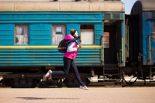 Young woman with backpack run at railway station. Travel by train