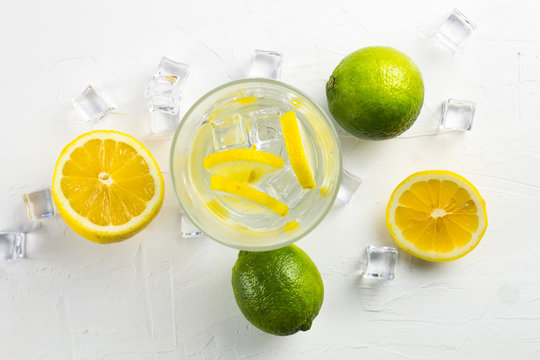 Fresh lemon and lime with glass and crystal ice cubes around. Close up.