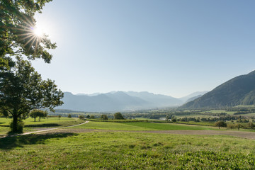 Wall Mural - panorama countryside view with sun shining and fields and forest and mountains in early autumn