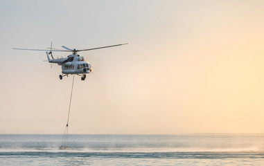 A helicopter with a red basket descends over the sea to scoop water against the background of the dawn orange sky and the silhouette of the city in the distance