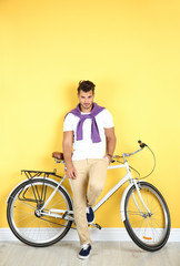 Handsome young hipster man with bicycle near yellow wall