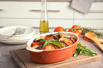 Baked eggplant with tomatoes, cheese and basil in dishware on table