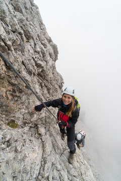 young climbers on a steep and exposed rock face climbing a Via Ferrata