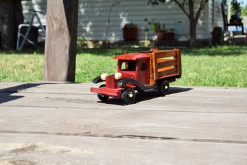 макет старинного автомобиля из дерева стоит на мосту