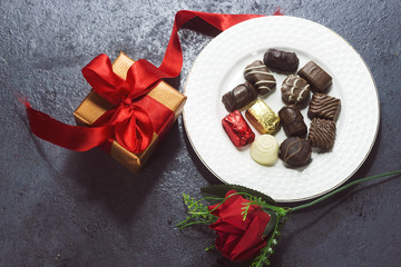 various chocolate and gift box on white plate, small gift box with  red ribbon and flower  for valentine's day