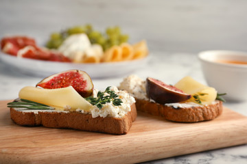 Sandwiches with ripe figs and cheese on wooden board, closeup
