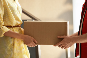 Woman receiving parcel from deliveryman on blurred background, closeup. Space for text