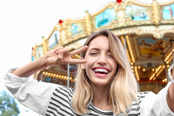 Attractive woman taking selfie in amusement park