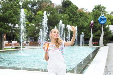 Attractive woman taking selfie near fountain in park