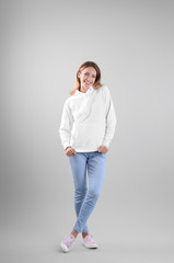 Full length portrait of woman in hoodie sweater on light background. Space for design