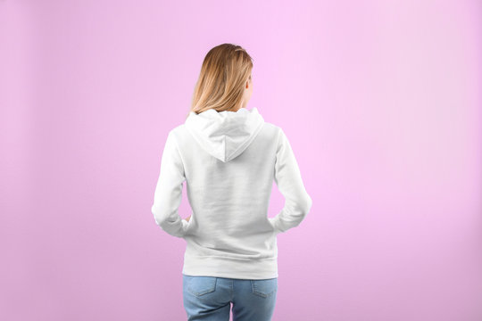 Woman in hoodie sweater on color background. Space for design