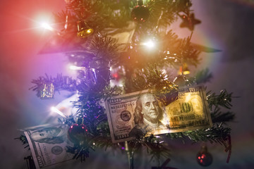 new-year fir tree is decorated with the 100 dollars. hundred-dollar bills laid out on the branches of the Christmas tree as a gift from Santa Claus.