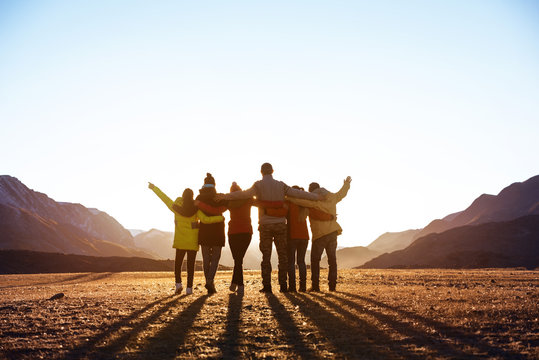 Group of friends against sunset mountains
