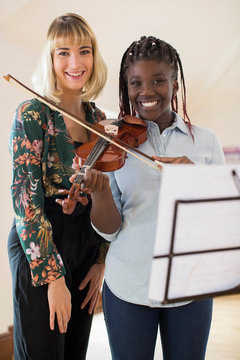 Portrait Of Female High School Teacher With Student Playing Violin In Music Lesson