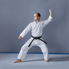 On a gray background an athlete in white karategi is doing formal karate exercises.