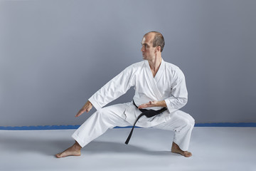On a gray background an athlete in a white karategi and with a black belt performs formal karate exercises.