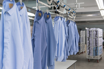 sewn new shirts hang on hangers in the textile factory workshop
