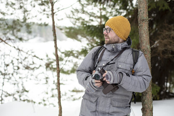 A bearded man with glasses holds a camera in his hands and stands leaning on a trunk of a young pine tree in a winter frosty forest, against the background of a lake, trees and snow.