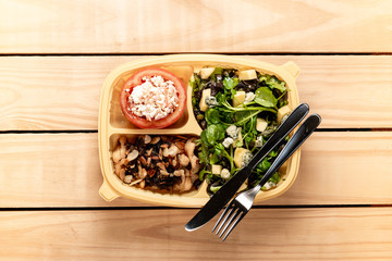 Salad and chicken strips with caramelized onions and almonds. Stuffed tomato. Brazilian lunch box. top view