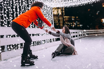Helping friend to stand up after fall on ice skates.