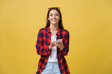 Portrait of Beautiful Young woman using mobile phone isolated on yellow background
