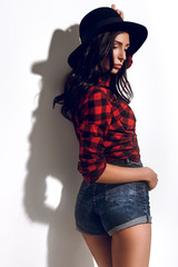 Brunette model, fashion model on a white background, model in a plaid shirt