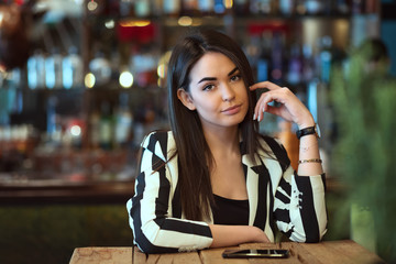 Beautiful brunette young woman wearing black and white jacket sitting alone at cafe table
