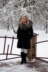 A woman is standing on the porch against a snowy forest. Winter and it's snowing