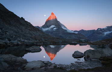 Fotomurales - The famous Riffelsee with the moon and the first sunlight shining on the Matterhorn.