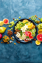 Healthy vegetarian bowl dish with fresh fruits and nuts. Plate with raw apple, orange, grapefruit, banana, kiwi, lemon, grape, almond, hazelnut and cashew nuts. Healthy balanced eating