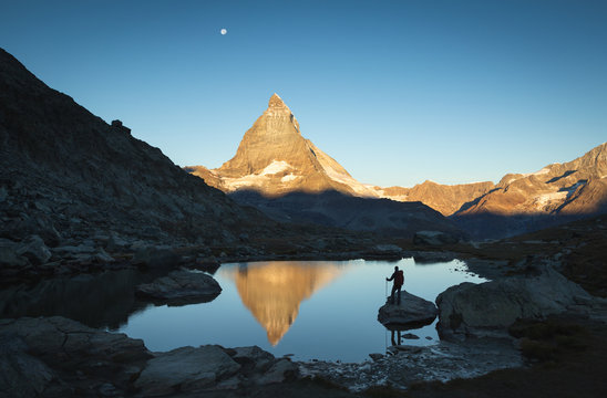 Hiker on a rock in the Riffelsee watching the first sunlight  on the Matterhorn.