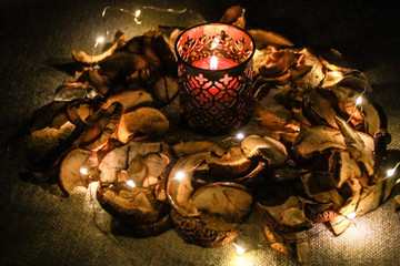 Night Helloween composition with dried apple and  candles.Warm and cold light.Garland.Autumn comfort.