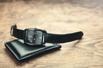 Wristwatch and wallet on wooden background.