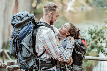 Looking at man. Curly beaming girlfriend looking at her handsome bearded man while trying Nordic walking with backpacks