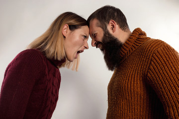 Close-up portrait screaming couple looking at each other, dressed in warm knitted sweaters. Isolated gray background