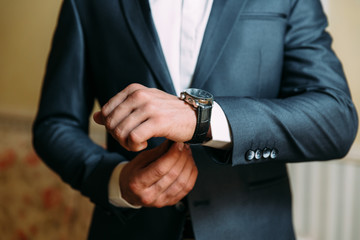 A close-up of a cropped frame of a man in an expensive classic costume looks at his watch. The businessman is in a hurry and looks at the time. A handsome man with a precious watch and a gold ring.