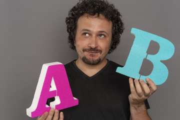 Optimization. conversion funnel, A / B test in marketing and online advertising. Brunette man holding colored letters A and B in hands with face expressions