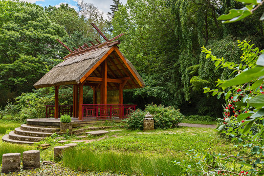 Shelter, wooden gazebo in the park and green grass