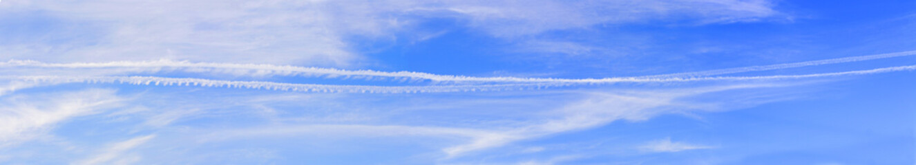 Large blue sky panorama with beautiful white and silver clouds and airplane tracks on the background-wide panoramic view in high resolution and quality