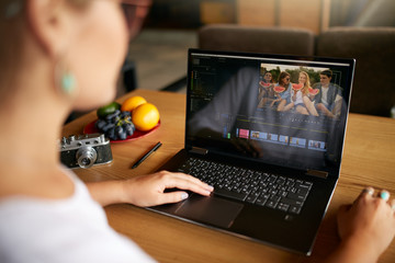 Freelancer video editor works at the laptop computer with movie editing software. Videographer vlogger or blogger camera man at work editing vlog. Tracking and revealing shot