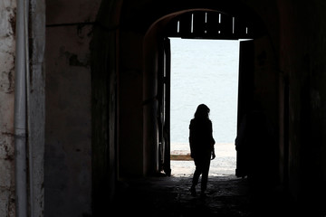 """U.S. first lady Melania Trump stands in the """"door of no return"""" where slaves past through, during a visit to Cape Coast castle"""
